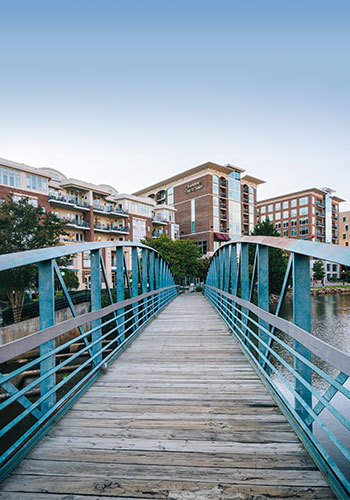 the blue metal footbridge crossing the Reedy River