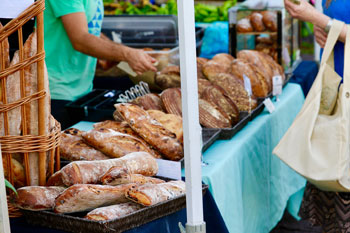 Fresh homemade bread on a table with a blue tablecloth at the downtown farmer's market
